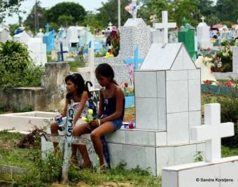 Wachten op hun moeder die bezig is een graf aan te harken.